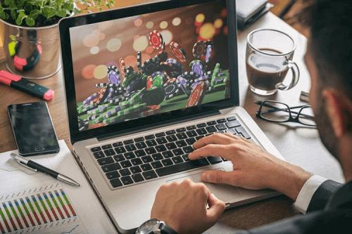 man at laptop playing casino game offshore
